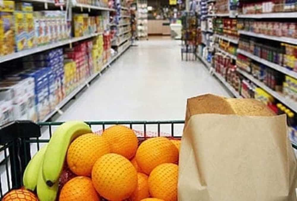 view of grocery store from grocery cart with oranges and bananas in the top section