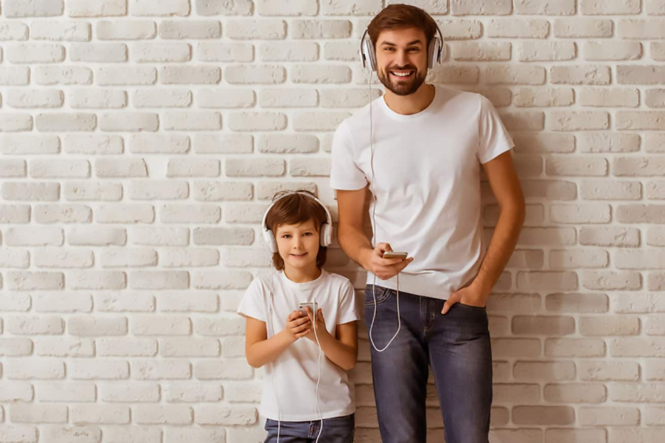 dad and child with headphones against white brick wall