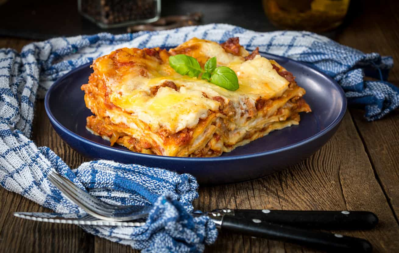Piece of tasty hot lasagna with red wine. Small depth of field.
