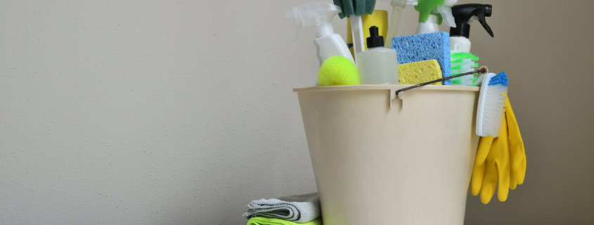 cleaning products in a bucket on white table