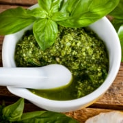 Homemade pesto sauce with basil and pine nuts in white mortar over old wooden table
