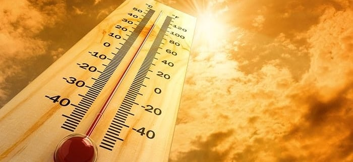 Large thermometer against orange-hot sun