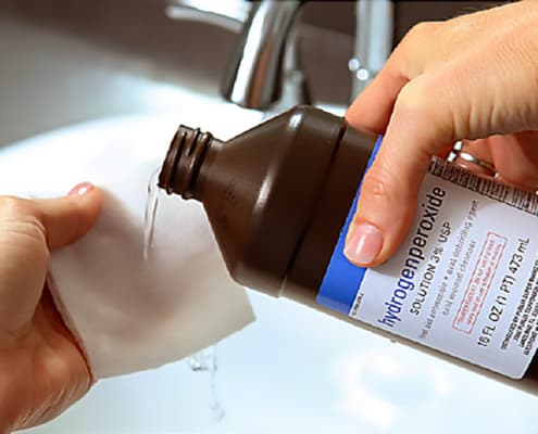 closeup of female hands pouring hydrogen peroxide into a clean cloth