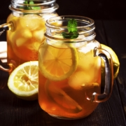 Black ice tea with lemon slice in glass jar on dark kitchen table background, summer cool soft drink, selective focus