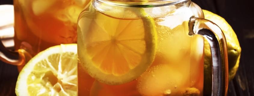 Black ice tea with lemon slice in glass jar on dark kitchen table background, summer cool soft drink, selective focus