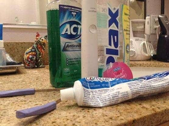 Bathroom counter showing dental care products