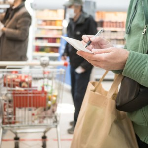 Woman with a shopping list at a grocery store with people shopping in the background