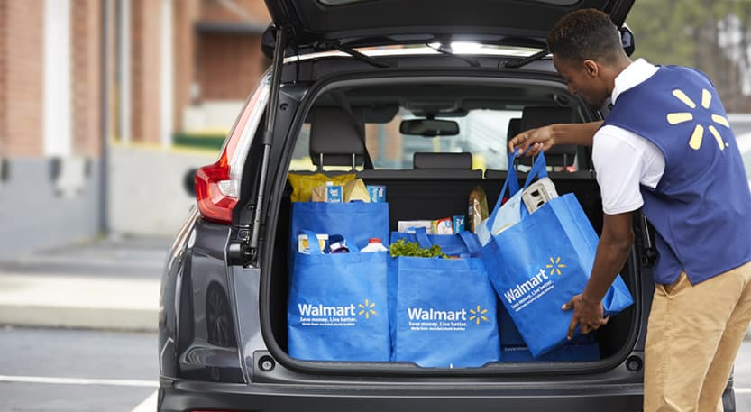 grocery shopping online from Walmart picking up groceries all loaded into the back of a car