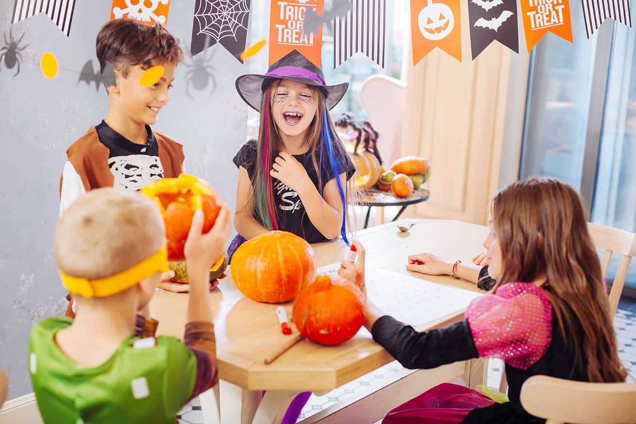 Halloween games. Four laughing emotional good-looking children wearing costumes playing funny Halloween games
