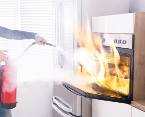 A person standing in front of a refrigerator, with Red Fire Extinguisher