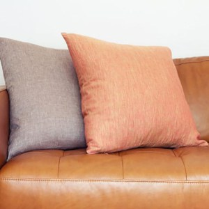 brown leather sofa with pillows of contrasting color