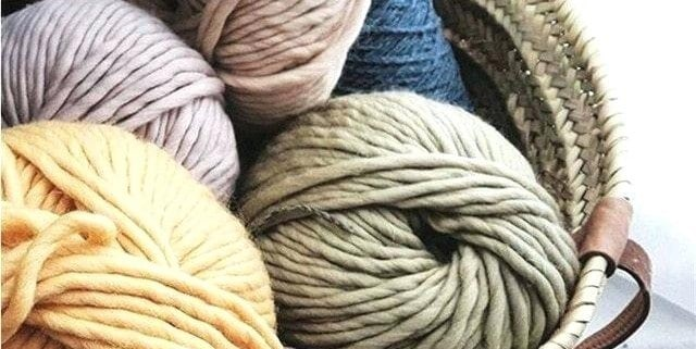 A basket of balls of feltable yarn in various colors to make wool dryer balls