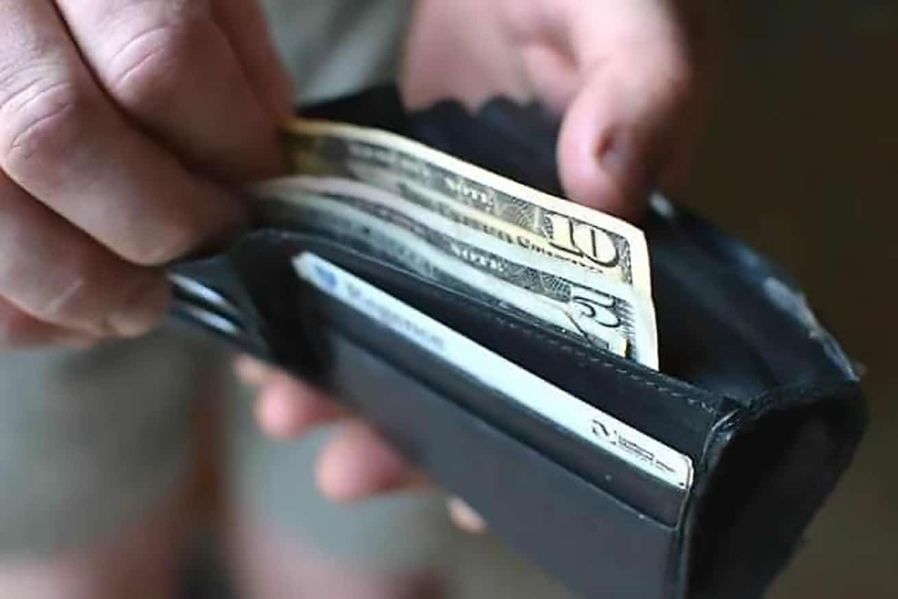 male hand opening wallet of money