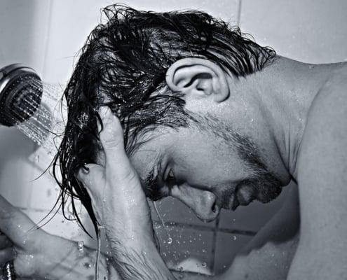 male in shower washing hair