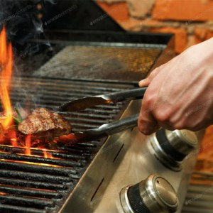 man cooking steaks on open grill
