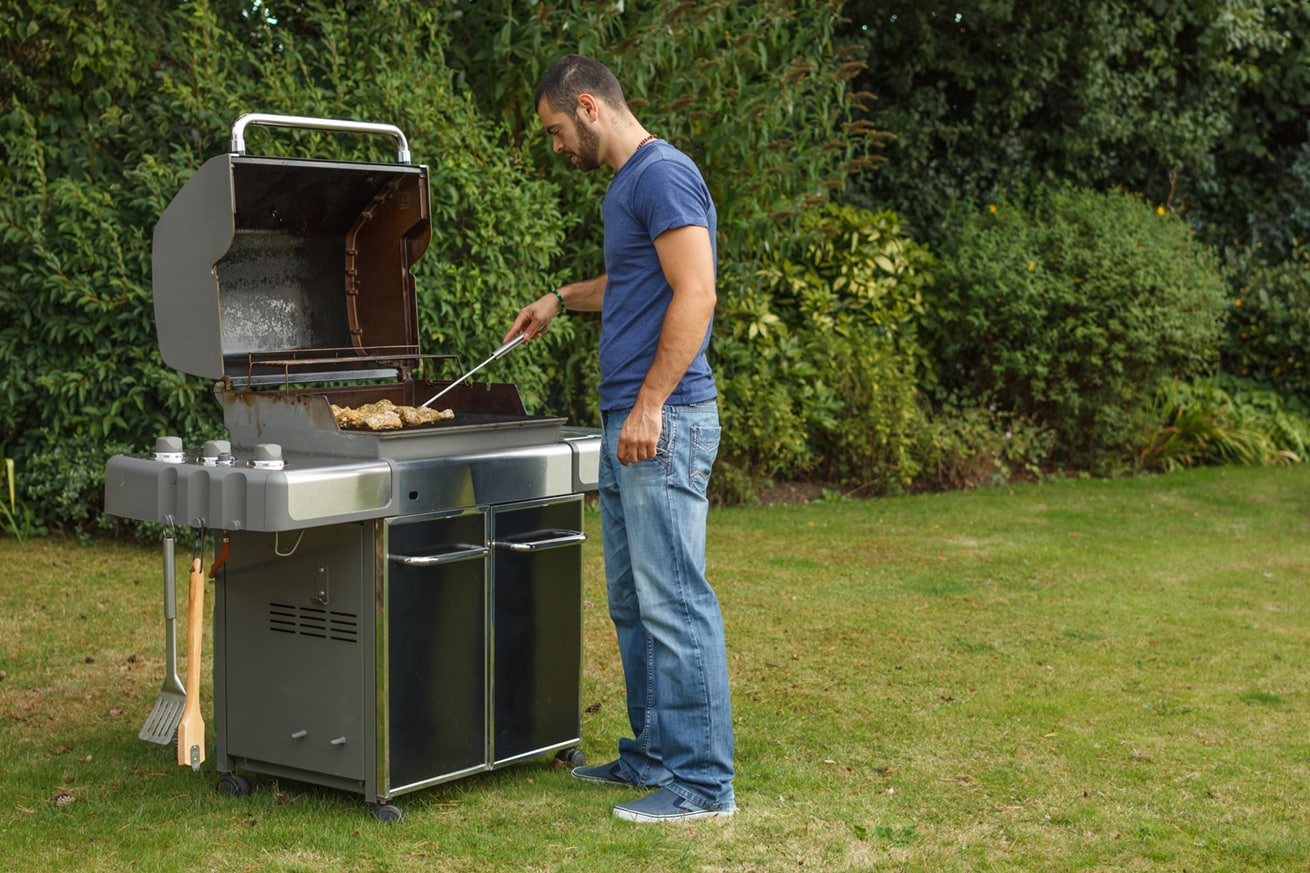 A man that is standing in the grass cooking on an outdoor grill