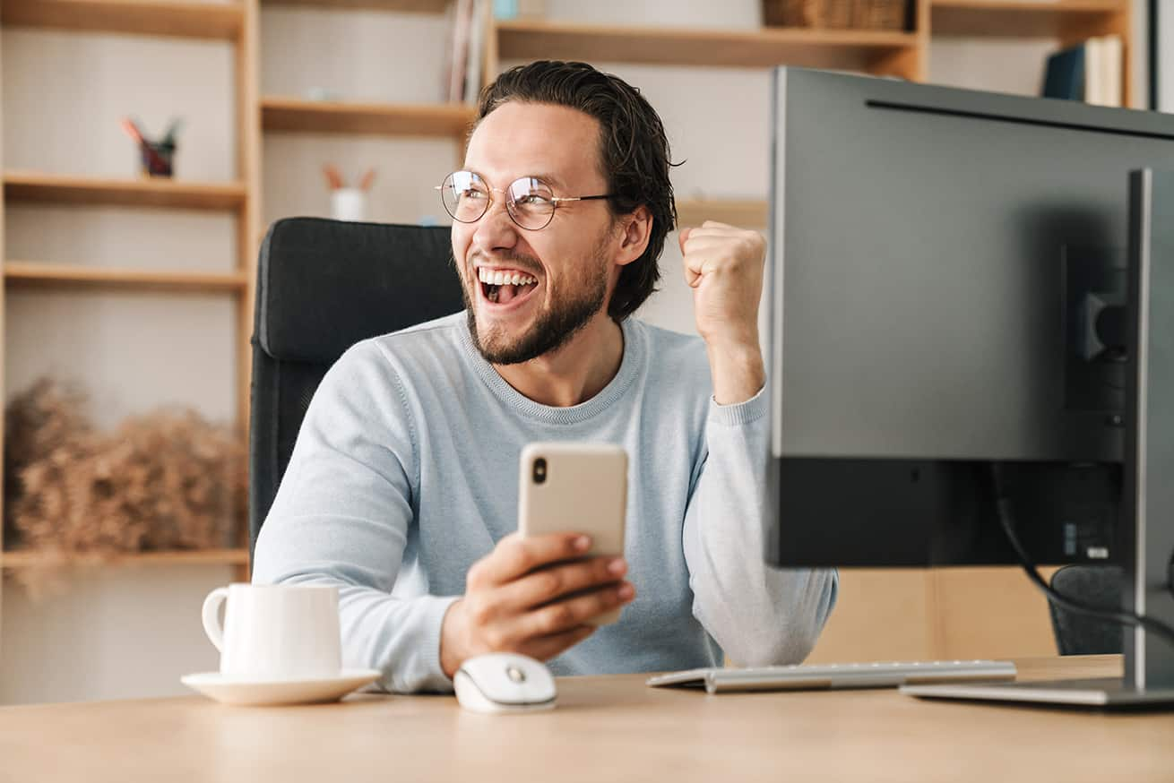 man seated at desk with phone in hand having just scored a big win