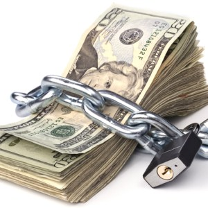 A stack of currency chained together and padlocked. Used for any money inference where money is tight or protected.