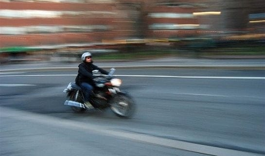 A man riding a motorcycle down a street