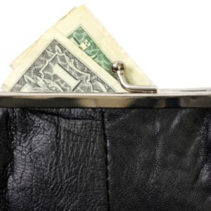 Black coin purse or wallet, with US one dollar bill.