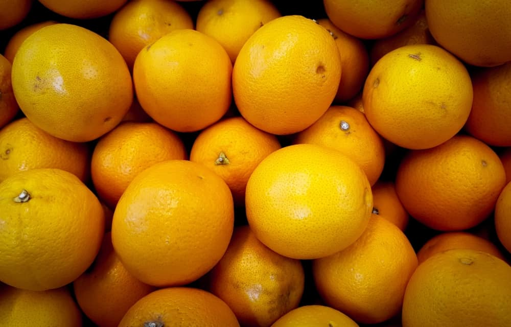 A pile of oranges sitting on top of a wooden table