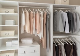 modern closet with clothes hanging on rail, white wooden wardrobe, interior design concept