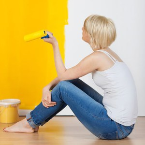 young casual woman with paint roller sitting on floor and looking at half yellow painted wall