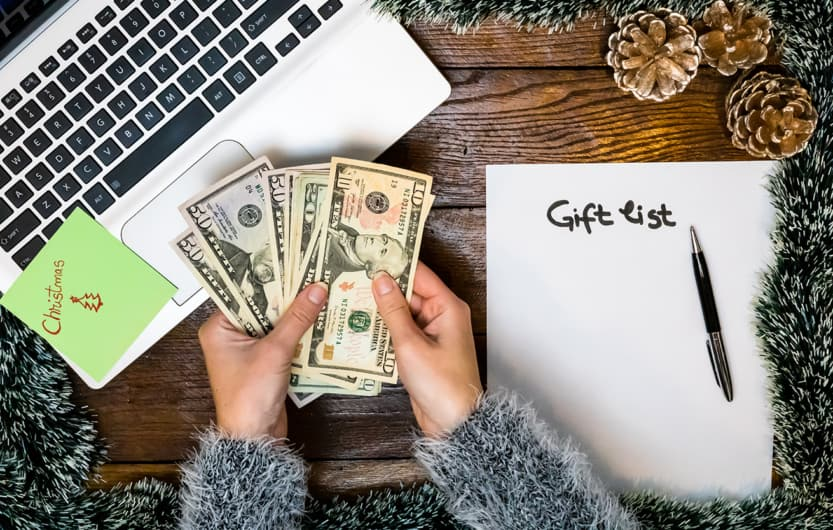 Hand holding money for buying Christmas gifts. Empty gift list on decorated office table. Top view of Christmas composition .