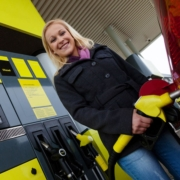a young woman at a gas station gasoline tank.