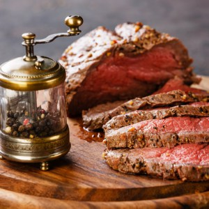 Roast beef on cutting board with saltcellar and pepper mill