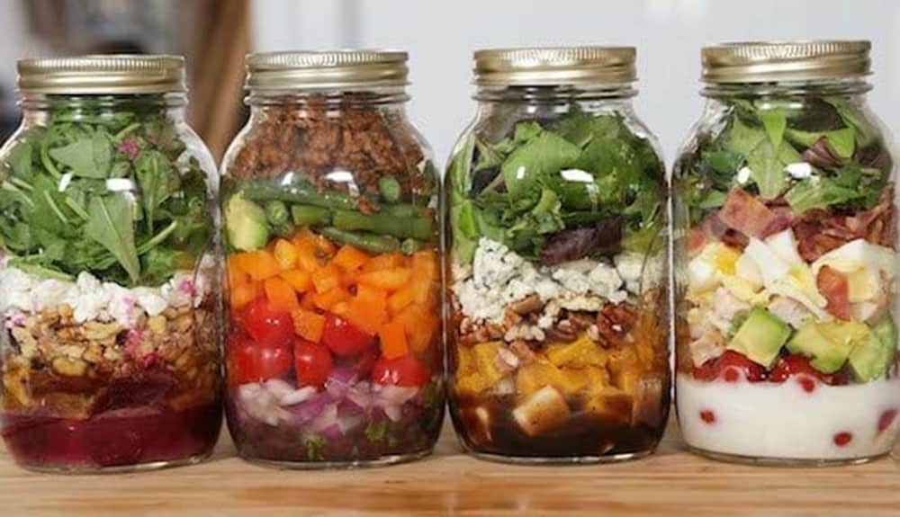 salad ingredients layered in glass canning jars