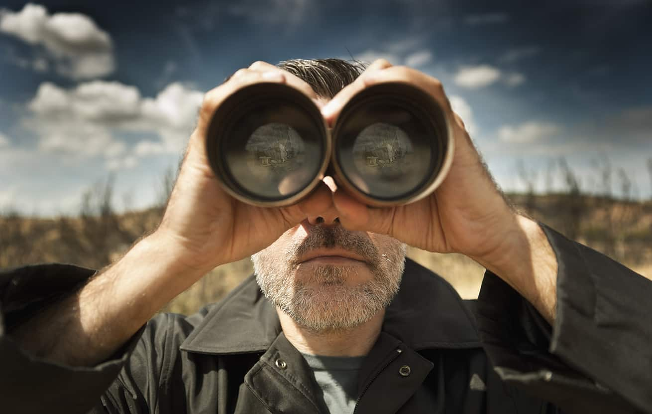 Man with binoculars in a field looking for money