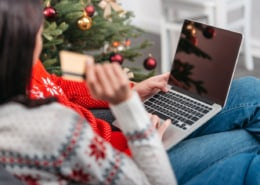 cropped shot of young couple shopping online with credit card and laptop at christmas