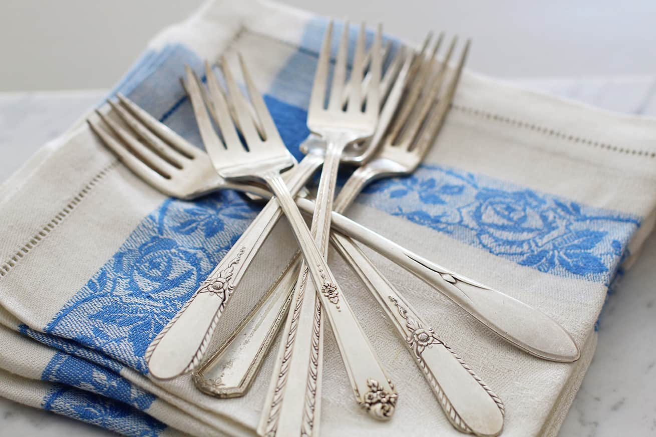 silver flatware forks on linen napkin