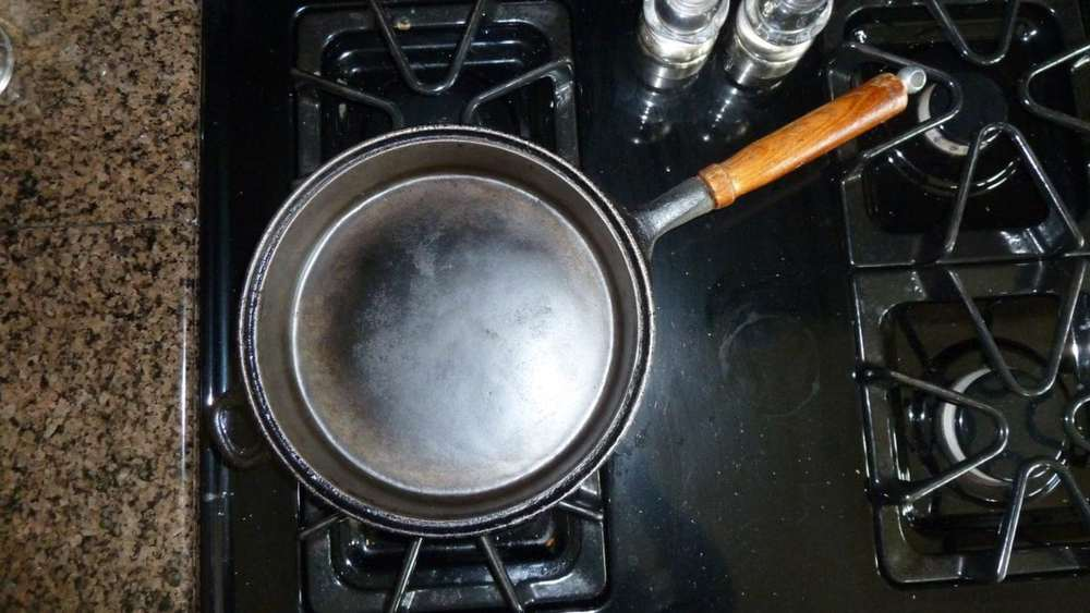 A dirty pan on a stove, with Cast iron