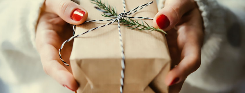 female hands holding small brown paper wrapped gift with sprig of fresh greenery