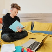 Software engineering student sitting on bed with books, laptop and textbooks around and writing in notebook