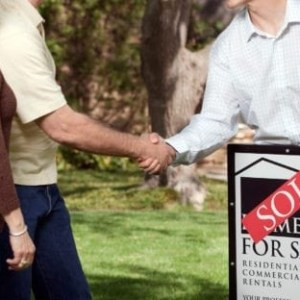 Buyers shaking hands with Realtor behind sold sign