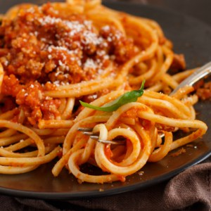 Spaghetti pasta with bolognese sauce on a dark table close up