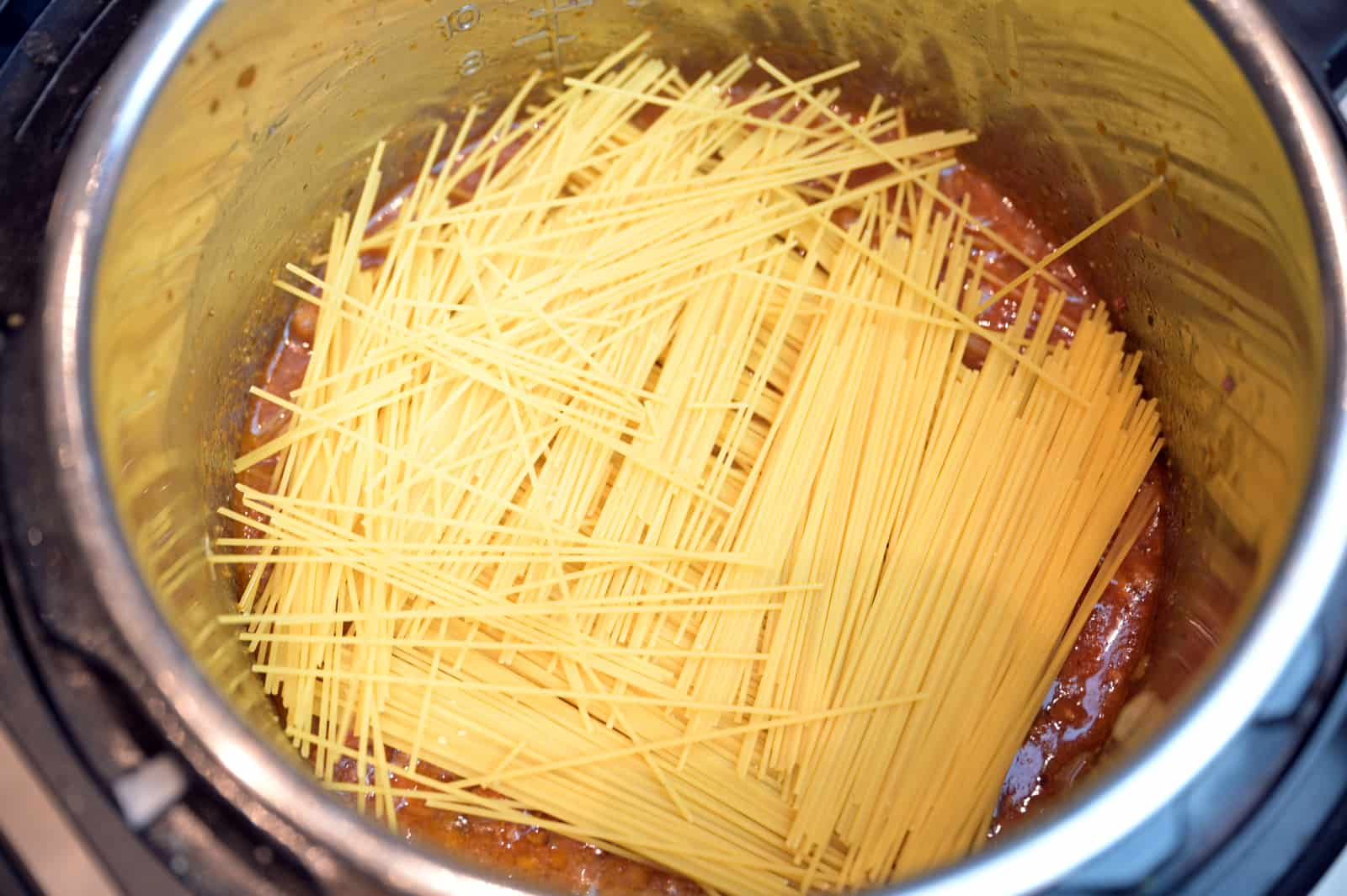 dry spaghetti broken in half and added in a criss cross pattern to Instant Pot