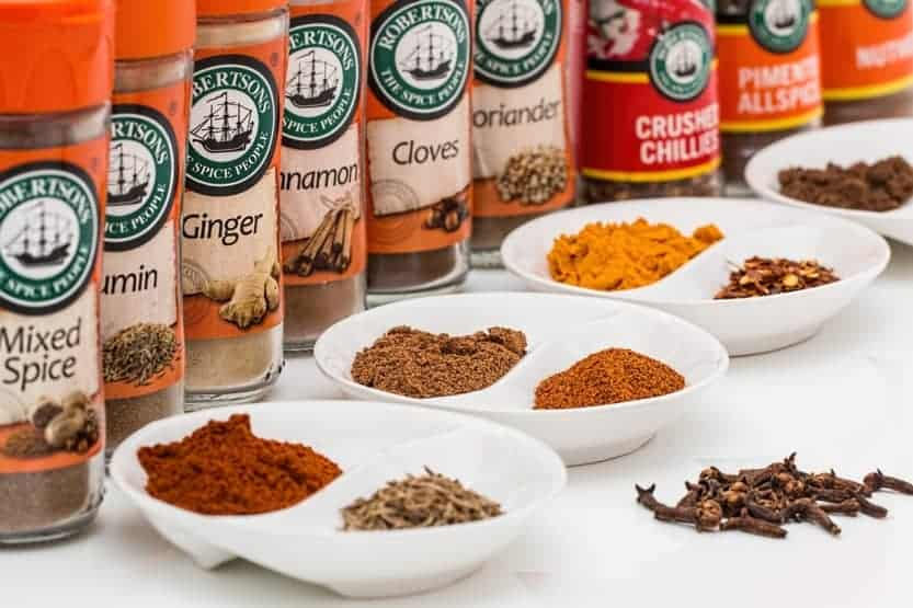 Spices in bottles and some poured out into small bowls