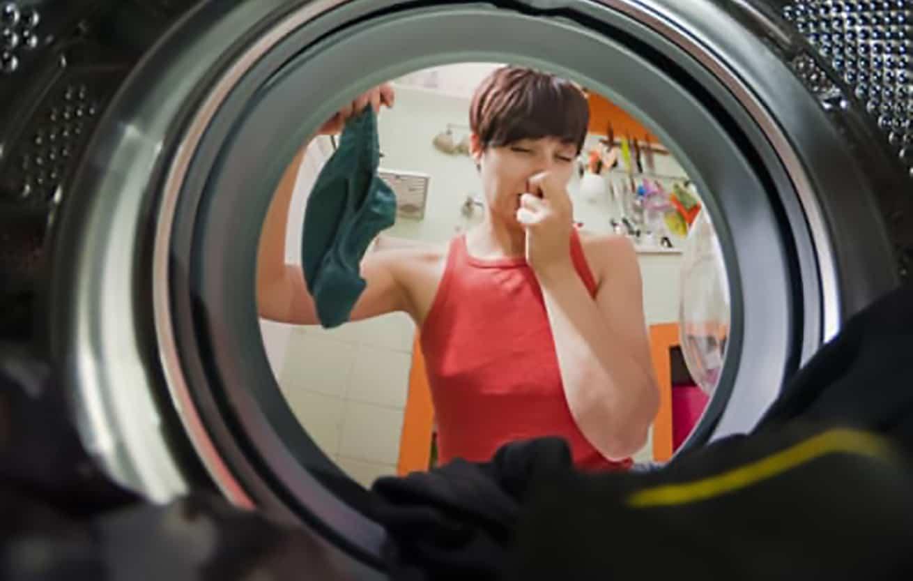 woman peering into stinky washing machine
