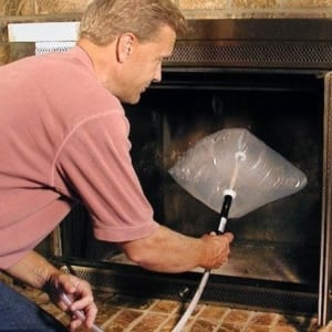 man inserting inflatable draft dodger in fireplace