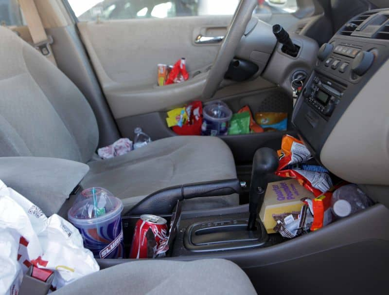Inside of a car with every nook and cranny stuffed with trash