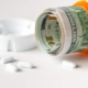 Healthcare cost concept using US Dollars with white medicine pills spilling from medicine bottle.