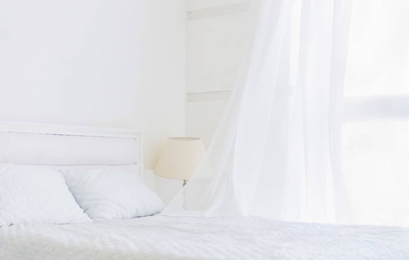 Abstract white room with white bed, waving curtain on window. White room minimal interior