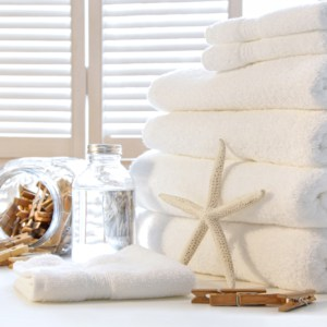 Fluffy white towels on table with shutter doors