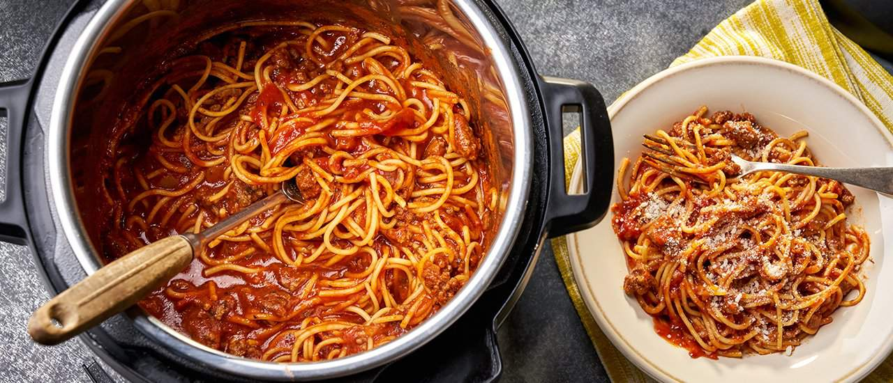 Instant Pot spaghetti with meat sauce in the pot with serving on the side