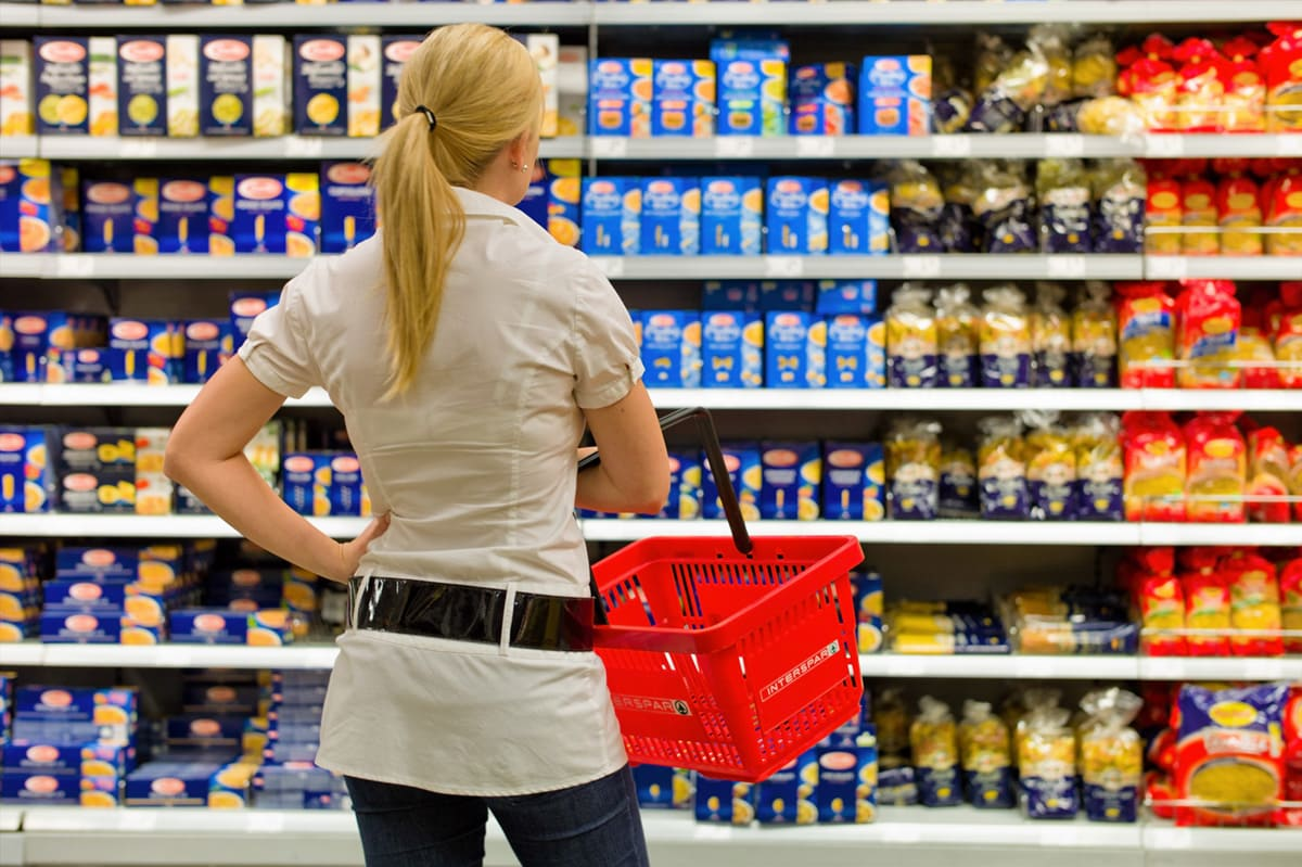 indecisive woman standing in grocery aisle holding an empty red grocery baske