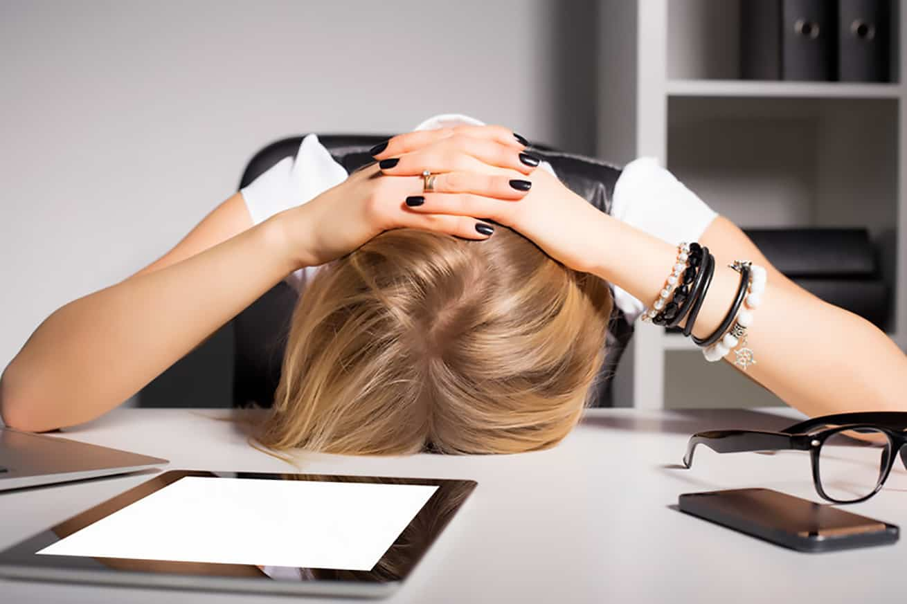 woman in despair with head on desk in office setting